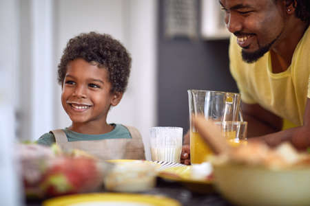 cute little african boy smiling, having breakfast with his dad, making funny face Foto de archivo