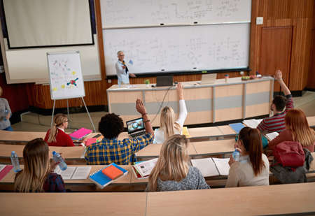 Female professor questioning students at a lecture in amphitheater