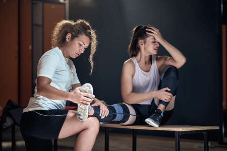 Young girl in locker room in pain due to injury on a training Stock Photo