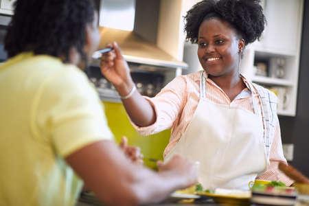 young afro-american couple eating, having fun. woman feeding his man, smiling