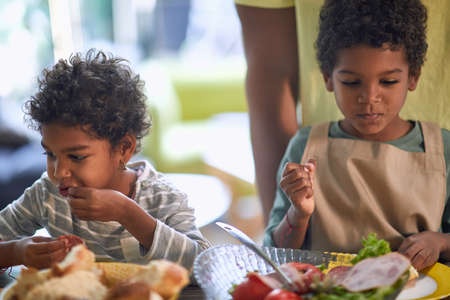 afro-american little girl and boy eating together with their fingers Foto de archivo