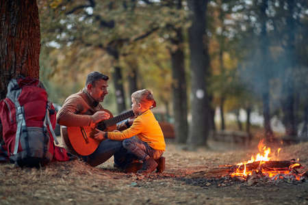Grandfather and grandson playing a guitar around campfire in the forest on a beautiful autumn dusk
