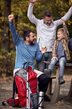 Cheerful father, son and grandson are happy together in the forest on a beautiful autumn day