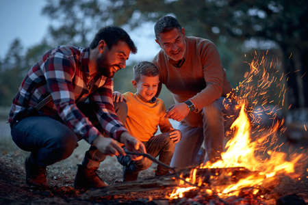 Father, son and grandson lit up a campfire in the forest on a beautiful autumn dusk Banco de Imagens