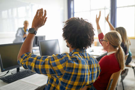 Students raising hands to answer the question at the lecture in university computer classroom