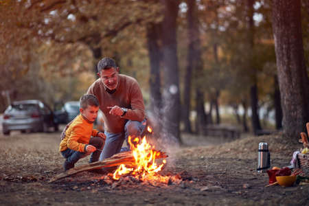 Grandfather and grandson enjoying a campfire in the forest on a beautiful autumn dusk Banco de Imagens