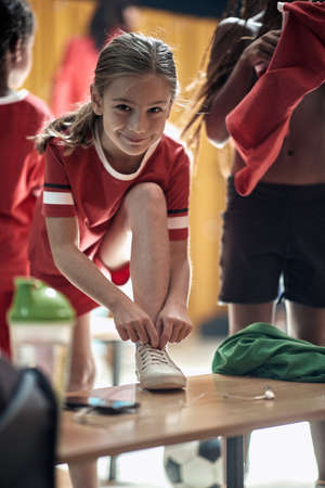 A little girl posing for a photo at the locker room while preparing for a training. Children team sport