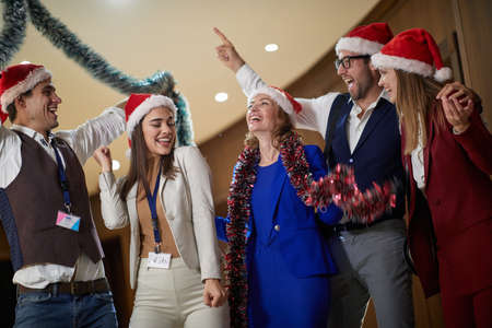 A group of excited colleagues making a holiday atmosphere at workplace on New Year's eve. Together, New Year, celebration Imagens