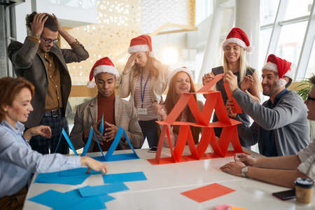 multiethnic group colleagues building paper towers at work in the office for christmas, playing