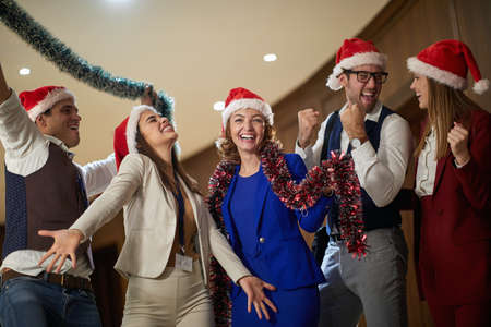 A group of excited colleagues celebrating end of year in the hallway in a holiday atmosphere at workplace. Together, New Year, celebration