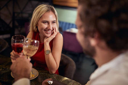 beautiful caucasian blonde toasting with a man, with in love look in her eyes