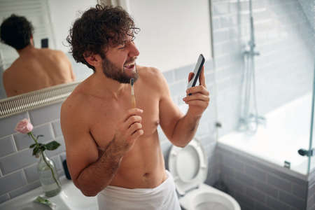 Jolly topless man texting while brushing teeth in the morning Stok Fotoğraf