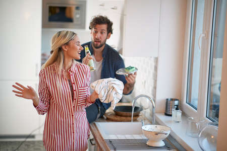 Young couple doing housework together in a cheerful atmosphere. Kitchen, housework, home, relationship Stok Fotoğraf