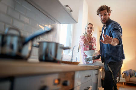 A young couple is posing for a photo while doing housework in a cheerful atmosphere. Kitchen, housework, home, relationship