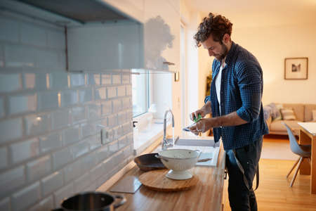 Young man washing dishes in a relaxed atmosphere in the kitchen. Kitchen, housework, quarantin, home