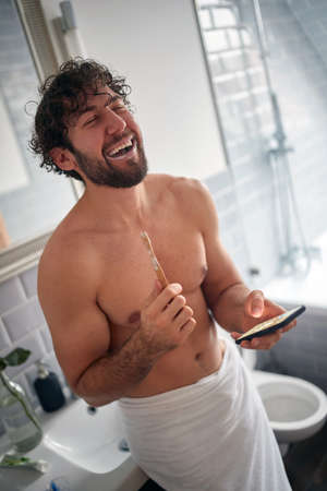 Smiling topless man texting while brushing teeth in the morning Stok Fotoğraf
