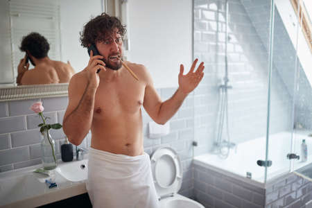 Topless man fighting while brushing teeth in the morning