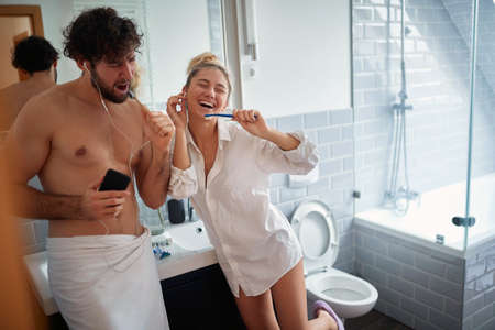 Happy couple brushing teeth together in the morning