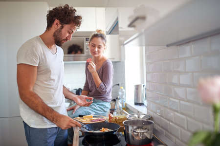 A young couple in love enjoying preparing breakfast together on a beautiful morning in the kitchen. Cooking, together, kitchen, relationship