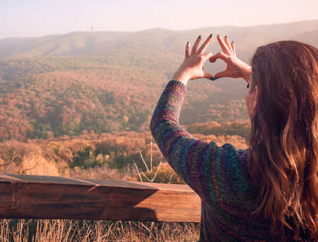 Woman making heart with her hands showing gratitude to nature and life. Happiness and freedom concept.