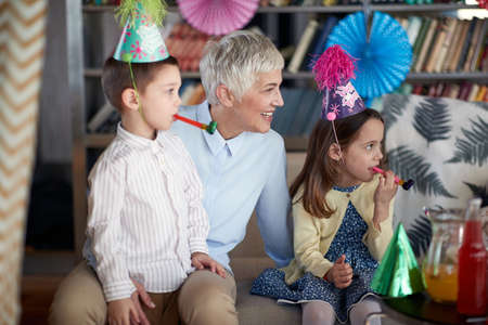Grandma enjoys a birthday party in a cheerful atmosphere at home with the grandchildren. Family, celebration, together