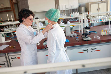 Young chemistry students are putting on protective gear while preparing for a work in a sterile laboratory environment. Science, chemistry, lab, people Standard-Bild