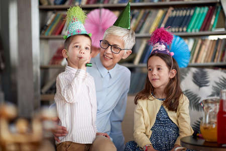 Grandchildren having a good time with their Grandma at a birthday party in a cheerful atmosphere at home. Family, celebration, together Standard-Bild