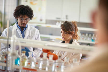 Young students working together with chemicals in a sterile environment of the laboratory. Science, chemicals, lab, people Standard-Bild