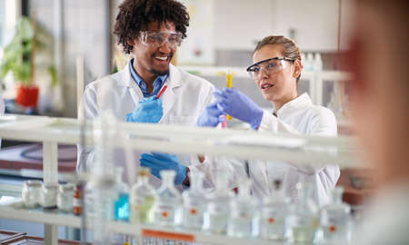 Two young medical students conducting chemical experiment in the lab Stock Photo