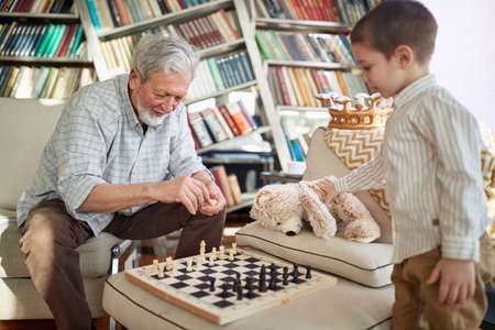 A little grandson loves playing the chess in a family atmosphere at home with his Grandpa. Family, leisure, together