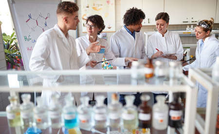 Team of young laboratory technicians discussing results in the lab Standard-Bild