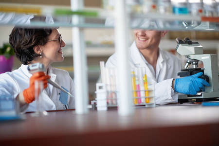 Young chemistry students are chatting while pipetting and microscoping in a laboratory in a relaxed atmosphere. Science, chemistry, lab, people