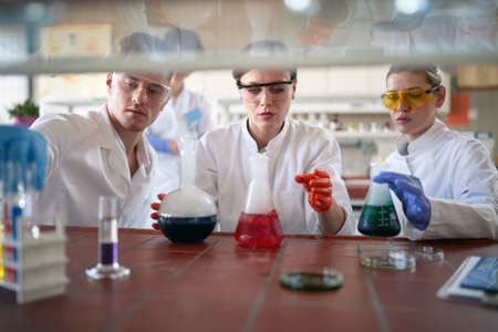 Young chemistry students work with caution while handling dangerous chemicals in a working atmosphere in the university laboratory. Science, chemistry, lab, people