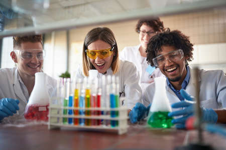 Young chemistry students having a good time in a sterile laboratory environment while enjoying observing colorful chemical reactions. Science, chemistry, lab, people