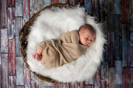 Sweet newborn baby sleeping in wooden basket on fluffy blanket