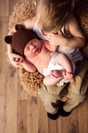 little boy holding his newborn brother