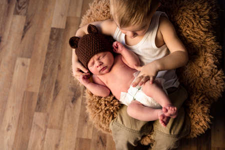 Little boy looking at sleeping newborn baby brother, love and family