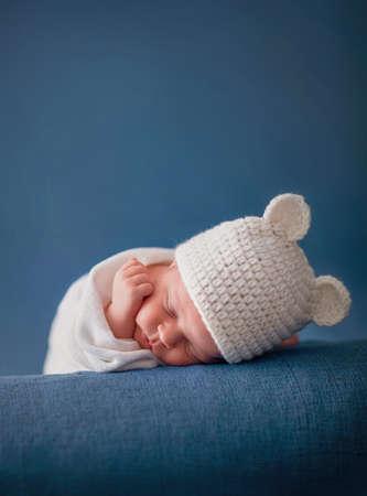 little newborn baby sleeping on a blue fur blanket with funny hat Standard-Bild