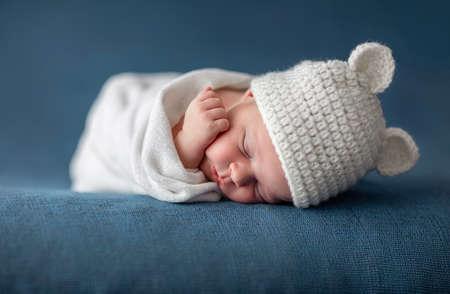 newborn boy baby sleeping with funny hat on a blue blanket
