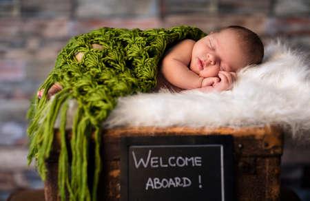 peaceful newborn baby sleeping on suitcases Standard-Bild
