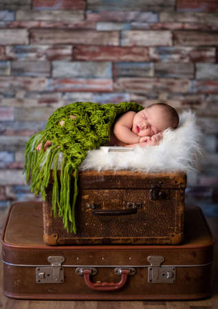little newborn baby is sleeping on a white fur blanket on top of rustic suitcases