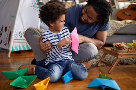 A young father and his cute little son spending a wonderful time together while playing with paper boats in a playful atmosphere at home. Family, home, playtime