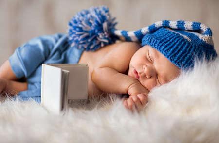Sleeping newborn baby in knitted cap on white fluffy soft blanket