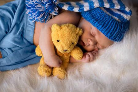 Serenity little newborn boy hugging teddy bear and sleeping