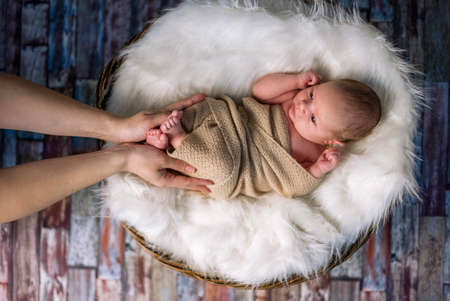 Baby legs in mother's hands, love touch