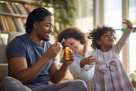 Joyful afro american parents playing with their daughter at home