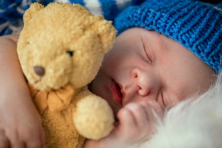 Sweet baby sleep in hug with teddy bear
