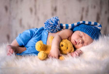 Newborn boy peacefully sleeping with his softy teddy bear Standard-Bild