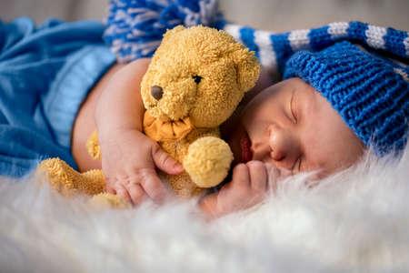 sleepy newborn baby with softy teddy bear on soft blanket