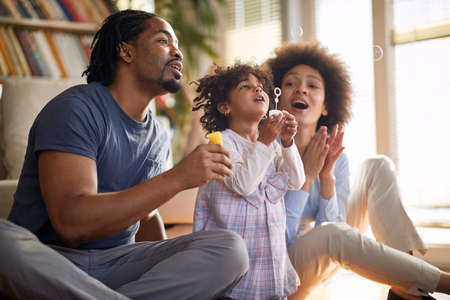 Young parents having a good time with their cute little daughter in a cheerful atmosphere at home while making soap bubbles together. Family, home, playtime